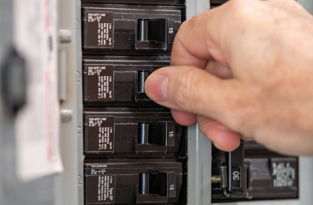 Male electrician turning off power for electrical outlet at circuit breaker box