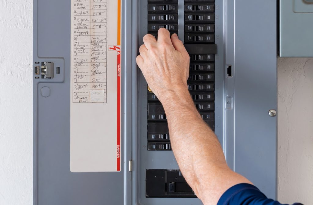 Mans hand switching residential electric panel
